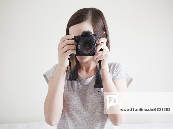 Young woman playing with digital camera