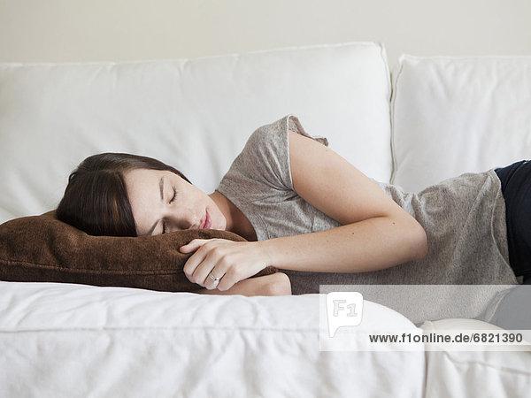 Junge Frau entspannt mit Buch neben sich auf braunem Sofa  lächelt