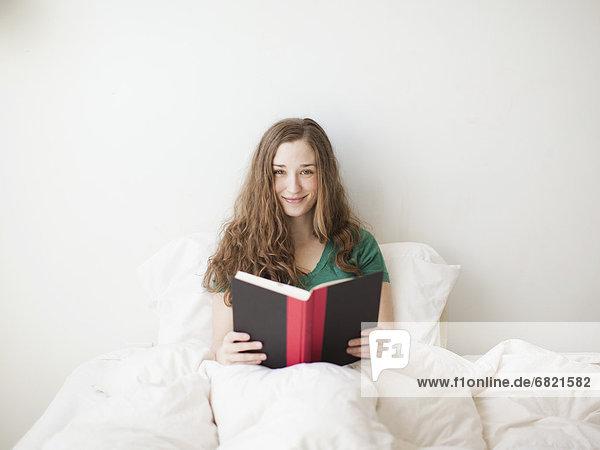 sitzend  Attraktivität  Frau  Fröhlichkeit  Buch  Bett  jung  Taschenbuch
