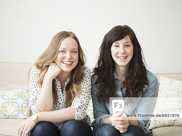 Two young female friends sitting on sofa