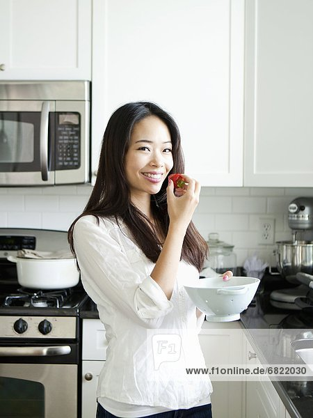 Portrait of smiling young woman eating strawberry in kitchen