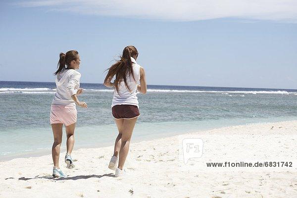 Young women jogging on beach  Guam USA