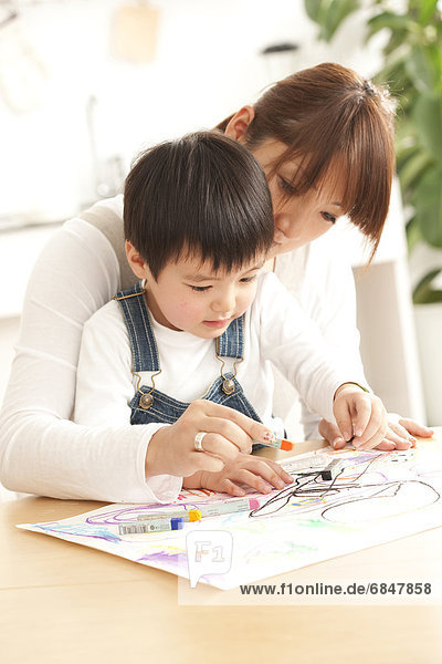 Mother and son drawing with crayon