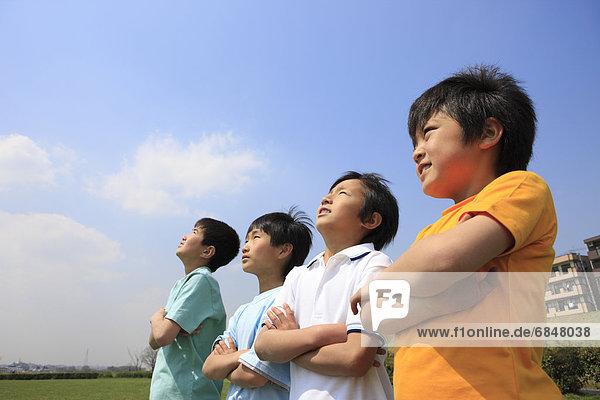 Four boys on field with arms crossed. Futako-tamagawa  Setagaya-ku  Tokyo Prefecture  Japan