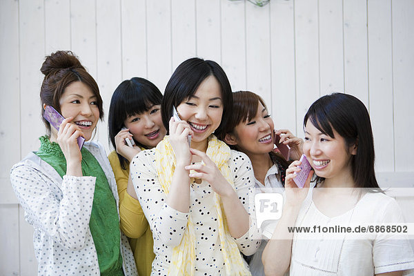 Five Young Women Talking on Phones