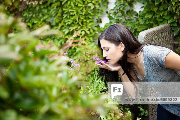 Junge Frau riecht Blume im Garten Junge Frau riecht Blume im Garten