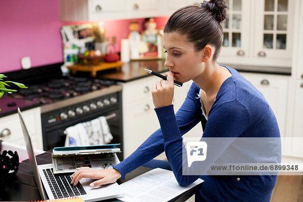 Junge Frau arbeitet von zu Hause aus am Laptop
