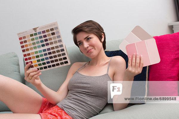Junge Frau auf dem Sofa beim Betrachten von Farbmustern