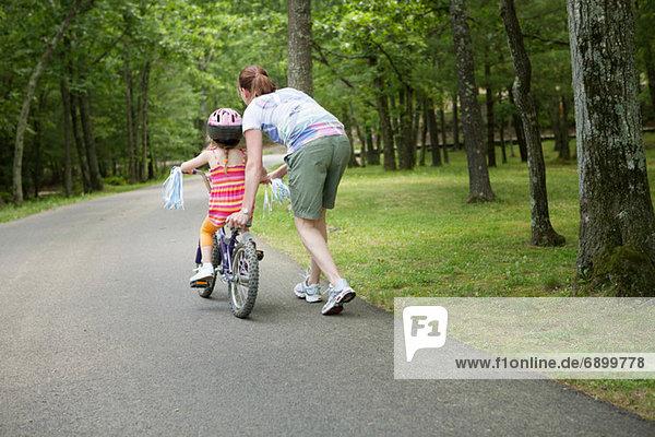 Mutter hilft Tochter beim Radfahren