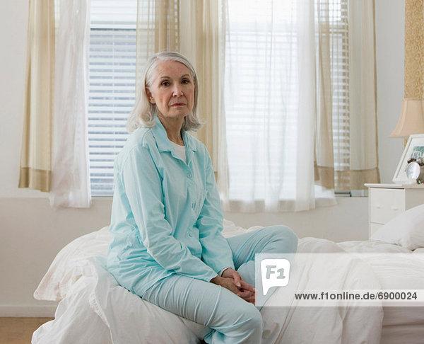 Porträt einer traurigen älteren Frau  die im Schlafanzug auf dem Bett sitzt.