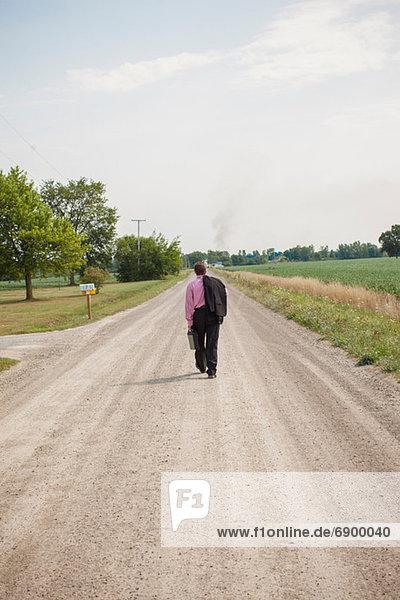 Ein Geschäftsmann  der eine unbefestigte Straße entlang geht.
