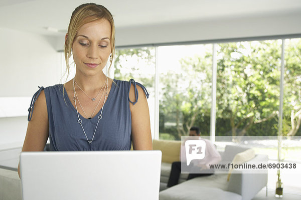 Woman Using Laptop  Man in Background