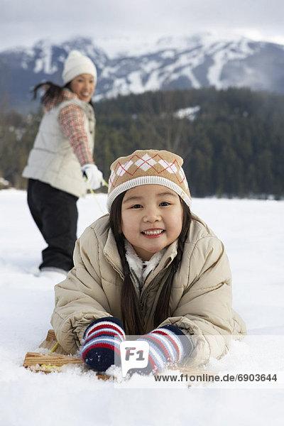 Woman Pulling Daughter on Toboggan  Whistler  British Columbia  Canada