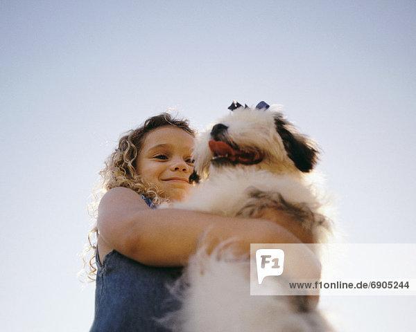 Girl Hugging Dog Outdoors