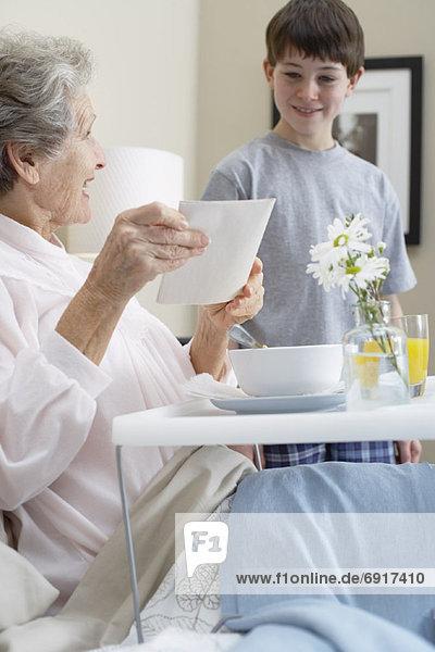 geben  Bett  Großmutter  Enkelsohn  Frühstück