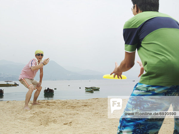 People Playing Frisbee On the Beach