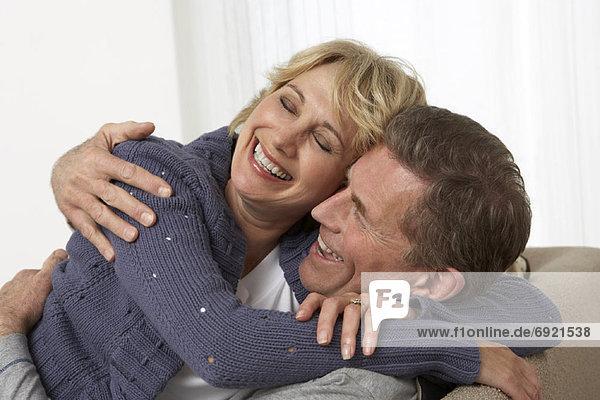 Paar umarmt auf Sofa