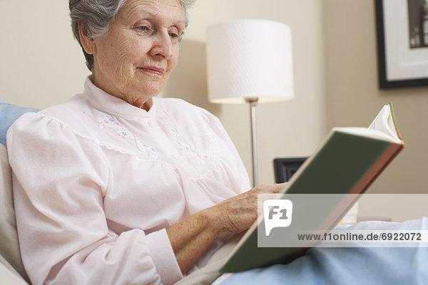Frau  Buch  Bett  Taschenbuch  vorlesen
