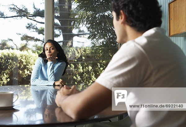 Couple Sitting At Kitchen Table