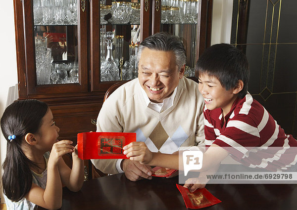 Grandfather with Grandchildren Holding Ang Pow Envelopes
