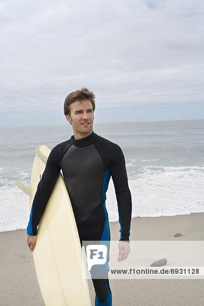 Mann  hält Surfboard