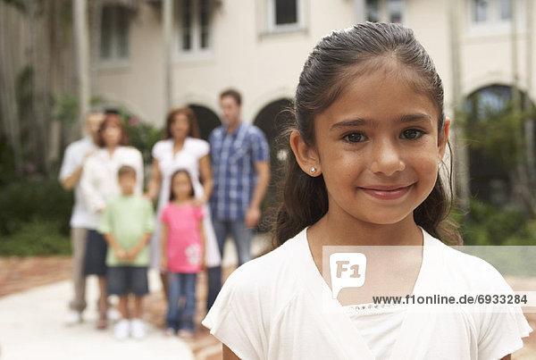Portrait of Little Girl  Family in Background