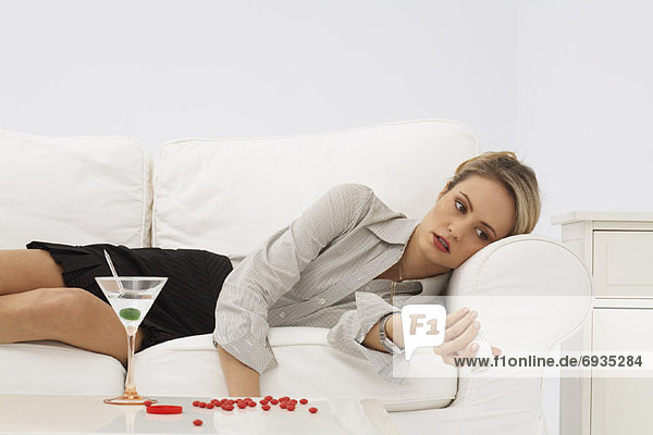 Businesswoman Lying on Sofa  with Pills and Martini
