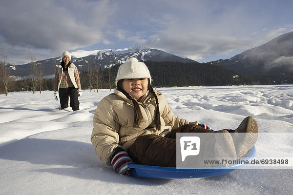 Mother and Daughter Sledding  Whistler  British Columbia  Canada