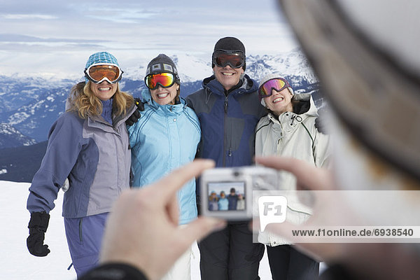 Person Taking Picture of Friends On Ski Hill  Whistler  BC  Canada