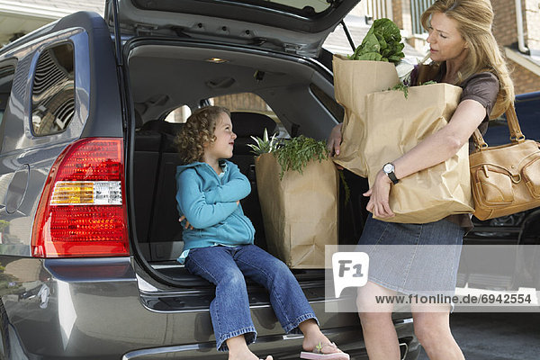 Mother with Daughter,  Removing Groceries from Car