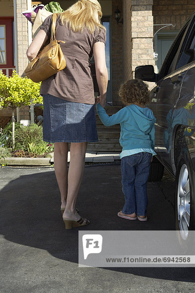 Woman Holding Daughters Hand  Walking into House