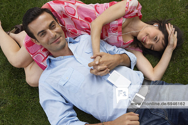 Couple Lying on Grass  Listening to Mp3 Player