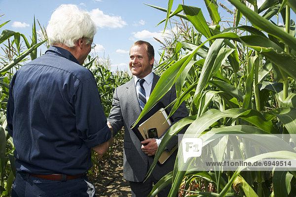 Farmer and Businessman in Cornfield