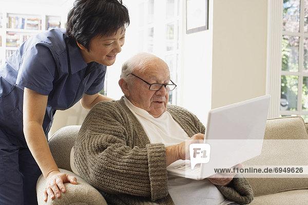 Senior Senioren benutzen Frau Mann Computer Notebook sehen über