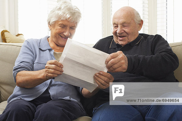Senior Couple Sitting on Sofa Looking at Document Together