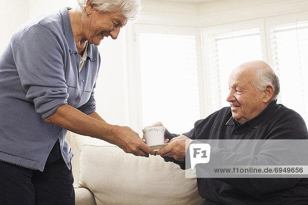 Senior Senioren Frau Mann geben Getränk