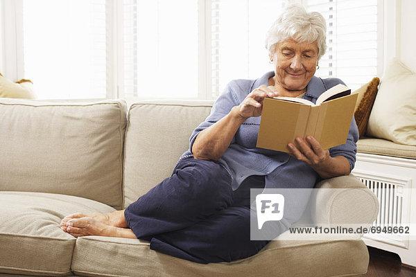 sitzend Senior Senioren Frau Couch Buch Taschenbuch vorlesen