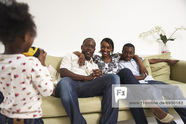 Girl Taking Picture of Family on Sofa