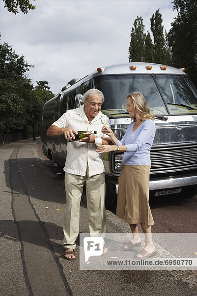 Couple Standing by Trailer  Celebrating With Champagne