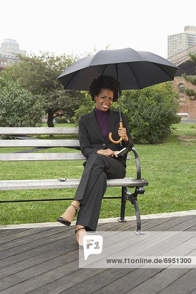Vereinigte Staaten von Amerika  USA  New York City  Geschäftsfrau  Regen  Sitzbank  Bank