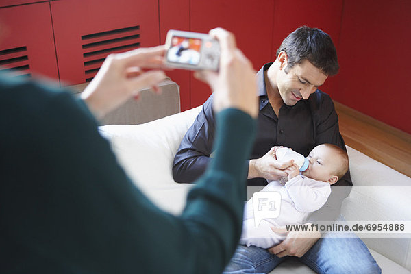 Woman Taking Picture of Man with Baby