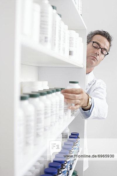 Pharmacist Taking Pills From Shelf
