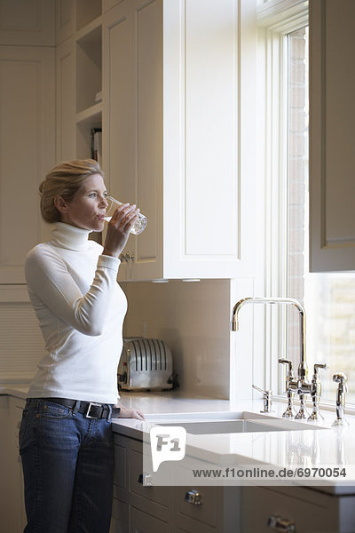 Woman Filling Glass from Kitchen Faucet