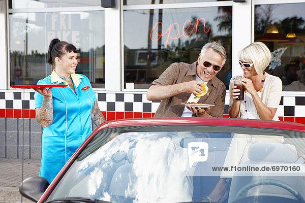 Waitress Serving Couple in Their Convertible at a Retro Diner  Niagara Falls  Ontario  Canada