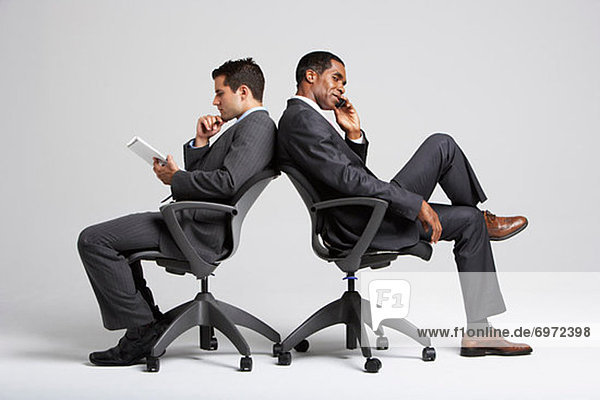 Businessmen Sitting Back to Back in Office Chairs