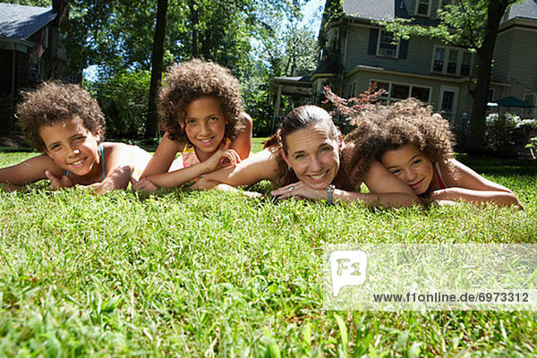 Portrait of Mother and Children Laying on Grass