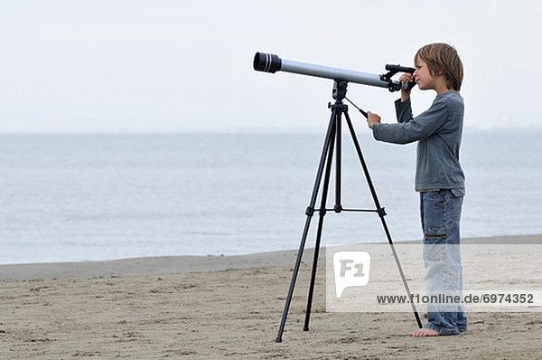 Boy on Beach Looking Through Telescope