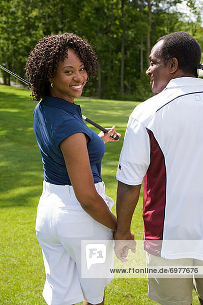 Backview of Couple Walking on Golf Course