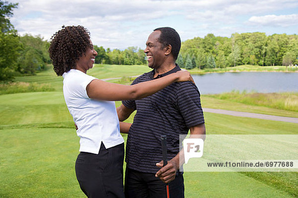 Couple Embracing on Golf Course