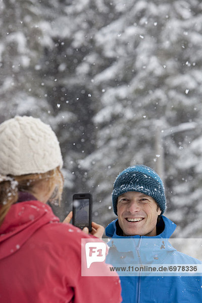 Woman Taking Picture of Man with Camera Phone Outdoors in Winter  Whistler  British Columbia  Canada